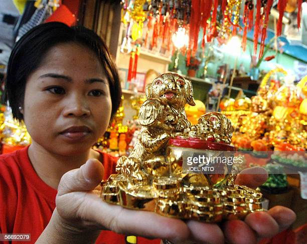 A vendor in Chinatown in the Philippine capital 28 January 2006 shows dog figures for sale for the coming Chinese New Year celebrations ushering in...