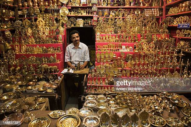 Vendor in Shree Menakshi Temple selling religious paraphenelia made from brass.