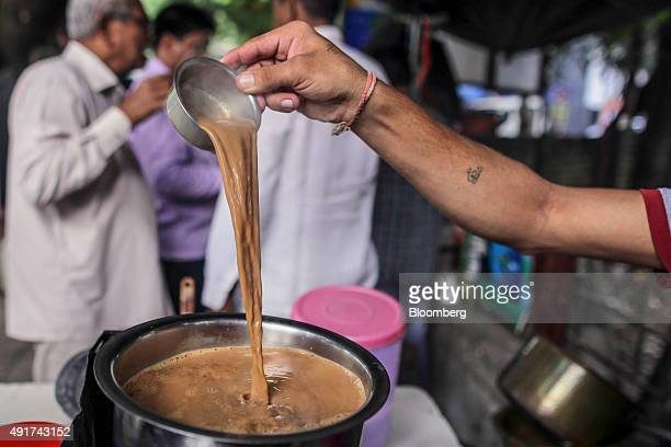 A vendor ladles chai while preparing the spiced tea at a roadside stall in Mumbai India on Friday Sept 25 2015 That sweet and milky tea concoction...