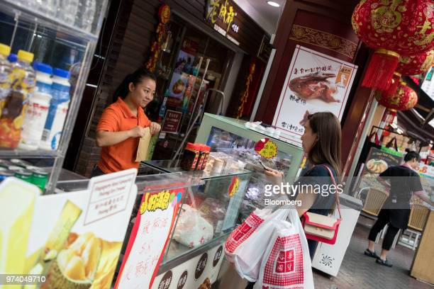 A vendor left talks to a customer at a stall in the Chinatown area of Singapore on Wednesday June 13 2018 Tourism as well as the consumer sector will...