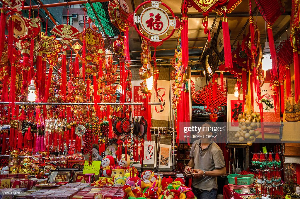 A vendor looks at his display of Chinese New Year items for sale at a street market in Hong Kong on January 31, 2013. The Chinese New Year of the snake falls on February 10, 2013. AFP PHOTO / Philippe Lopez
