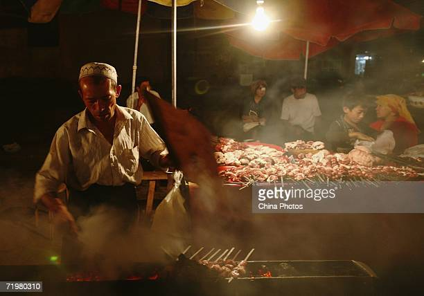 A vendor makes shashlik at a booth on September 20 2006 in Kashi of Xinjiang Uygur Autonomous Region northwest China Kashi is an oasis city which has...