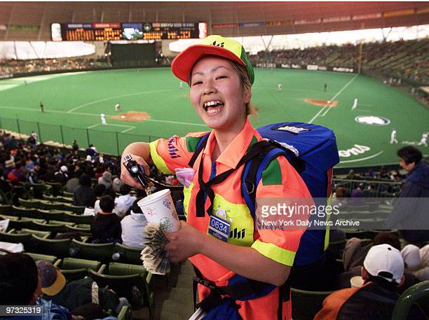 Vendor Mariko Toko dispenses beer from a minikeg in a backpack at game between the New York Mets and the Seibu Lions at the Seibu DomeThe Mets who...
