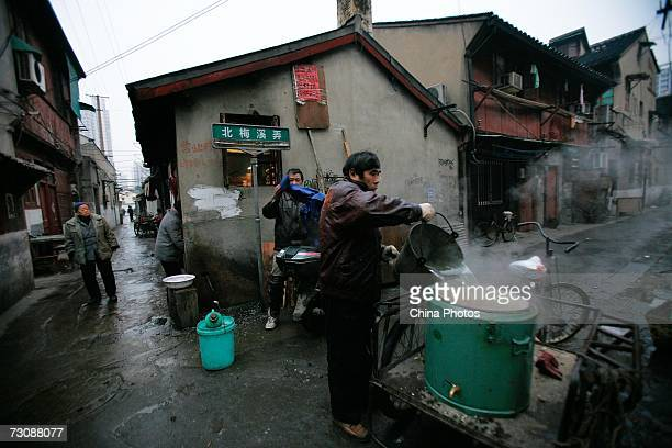 Vendor of a nearby store fetches hot water at a Laohuzao teahouse at an alleyway January 23, 2007 in Shanghai, China. Laohuzao is a traditional store...