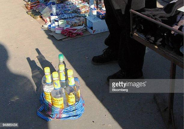 Vendor offers bootleg alcohol for sale at a market in central Warsaw Saturday, February 21, 2004. Rising living standards in Poland -- gross domestic...