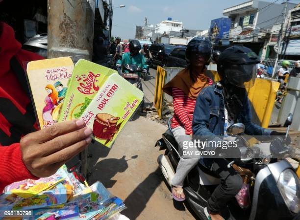 A vendor offers Eid cards to passing motorists in Jakarta on June 20 ahead of the Eid alFitr festival on June 25 Muslims throughout the world will...