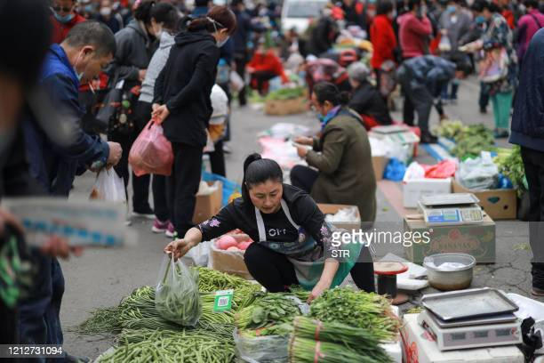 Vendor passes a bag of vegetables to a customer at a market in Shenyang in China's northeastern Liaoning province on May 12, 2020. - China's consumer...
