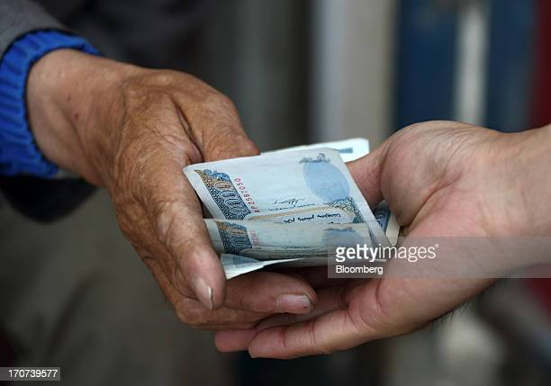 A vendor passes Mongolian onethousand tugrik banknotes to a customer as change at a stall in Dalanzadgad Mongolia on Wednesday June 5 2013 Mongolia a...