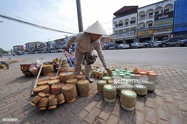 A vendor places handmade bamboo baskets for sale on the pavement of a street in downtown Vientiane on February 29 2008 Known as a sleepy city the Lao...