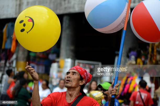 A vendor plays with a ball he is selling at the Divisoria market in Manila on January 23 2014 AFP PHOTO/NOEL CELIS