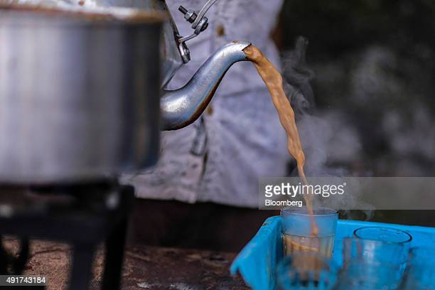 A vendor pours chai into glasses at a roadside stall in Mumbai India on Friday Sept 25 2015 That sweet and milky tea concoction called chai is...
