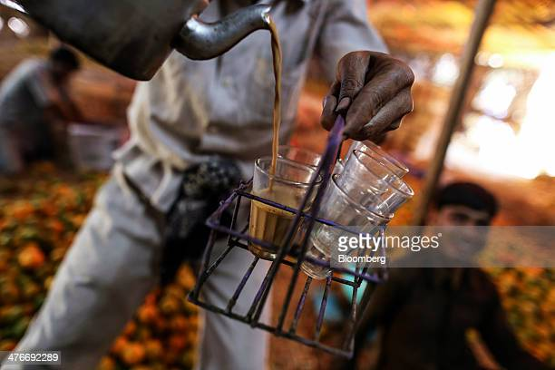 A vendor pours Indian chai tea into a glass for a photograph at a wholesale market in Nagpur Maharashtra India on Sunday March 2 2014 Indias economic...
