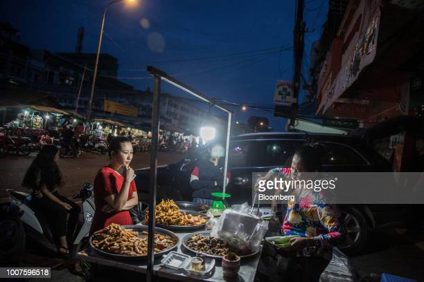 A vendor prepares food for a customer at a roadside stall at night in Phnom Penh Cambodia on Sunday July 29 2018 Cambodian Prime MinisterHun...
