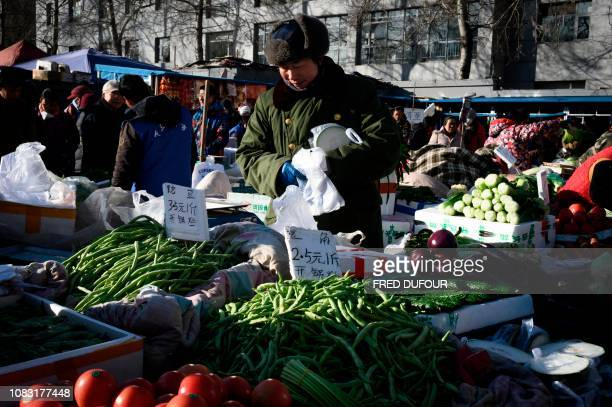 A vendor prepares food to sell at a market in the center of Beijing on January 16 2019 China's GDP growth may be significantly slower than official...