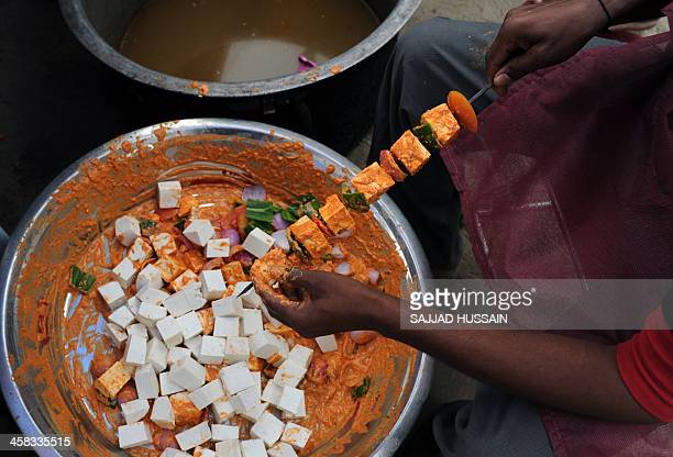 A vendor prepares paneer tikka a grilled vegetarian dish made with vegetables and paneer during the National Street Food Festival at Jawaharlal Nehru...