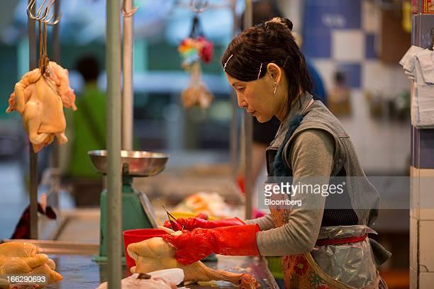 A vendor prepares slaughtered chicken at a stall at the Kowloon City Market in Hong Kong China on Thursday April 11 2013 The Hang Seng Index rose 08...