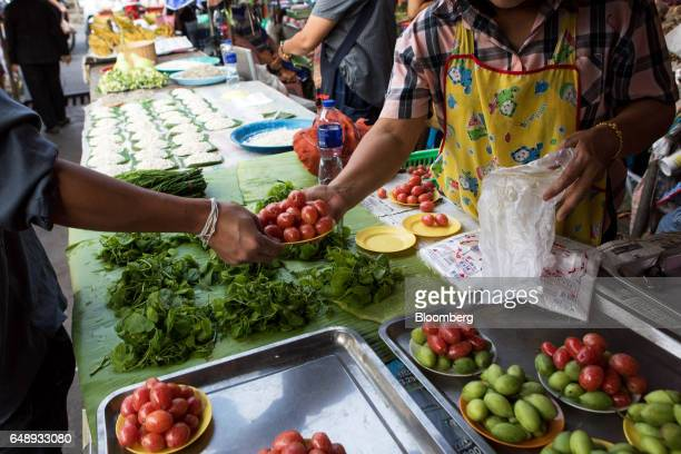 A vendor prepares to pack a plate of cherry tomatoes into a plastic bag at a street market stall in Nan Nan Province Thailand on Friday March 3 2017...