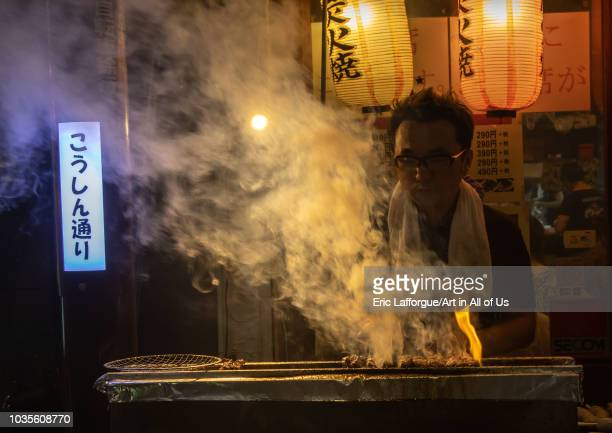 Vendor preparing food on barbecue grill at street market, Kanto region, Tokyo, Japan on August 26, 2018 in Tokyo, Japan.