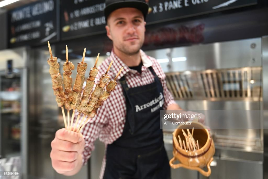 A vendor presents special Italian sheep 'kebab' at a stand during a press tour at FICO Eataly World agri-food park in Bologna on November 9, 2017. Eataly World, said to be the world's biggest agri-food park, will open to the public on November 15, 2017. The free entry park, widely described as the Disney World of Italian food, is ten hectares big and will enshrine all the Italian food biodiversity. / AFP PHOTO / Vincenzo PINTO