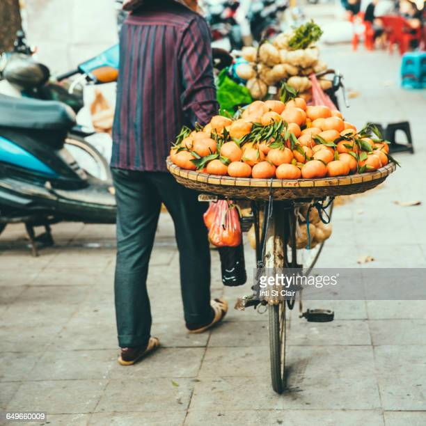 Vendor pushing bicycle with fruit for sale