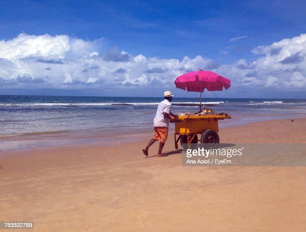 Vendor Pushing Concession Cart At Beach Against Sky