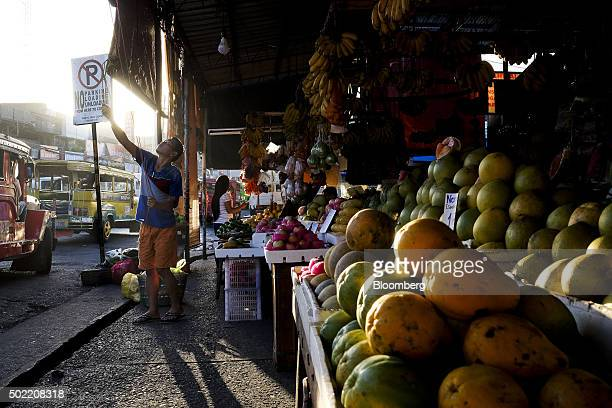 A vendor raises the blinds at a fruit market stall in Davao Mindanao the Philippines on Saturday Dec 12 2015 Davao city's reputation as one of the...