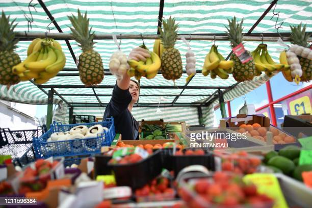 Vendor reaches for bananas at an outdoor fruit and vegetable stall in the London borough of Newham, east London, on May 2 as life in Britain...