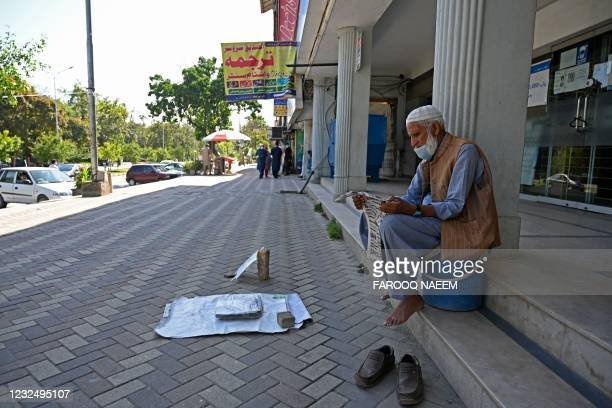 Vendor reads a newspaper while sitting in a closed market during a smart lockdown imposed as a preventive measure against the spread of the Covid-19...