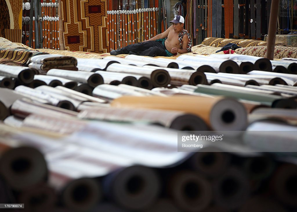 A vendor rests on rolls of carpet displayed for sale at a market in Ulaanbaatar, Mongolia, on Thursday, June 13, 2013. Mongolia, a country of almost 2.9 million people, is experiencing double-digit growth and new opportunities in the mining industry. Photographer: Tomohiro Ohsumi/Bloomberg via Getty Images