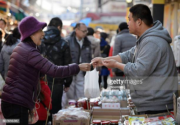A vendor right hands a customer her purchase at Ameyoko market in Tokyo Japan on Saturday Dec 26 2015 Japans consumer prices rose slightly in...