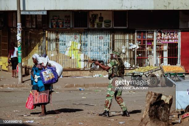 TOPSHOT A vendor scurries for cover with her wares as soldiers disperse demonstrators on August 1 2018 in Harare after protests erupted over alleged...
