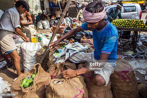 A vendor seals a sack of mangoes at his stall in a wholesale market in Lucknow Uttar Pradesh India on Saturday June 28 2014 Indian Prime Minister...