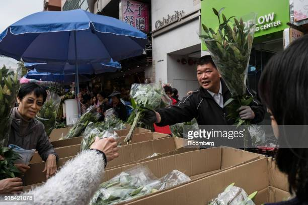 A vendor second right hands a bouquet to a customer at a flower market ahead of Lunar New Year in the Mong Kok district of Hong Kong China on...