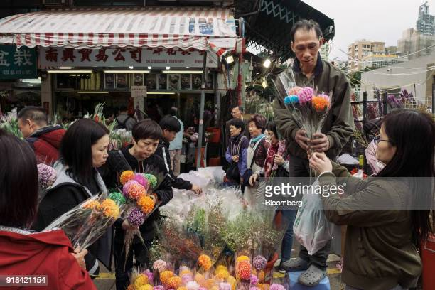 A vendor second right hands bouquets to a customer at a flower market ahead of Lunar New Year in the Mong Kok district of Hong Kong China on...