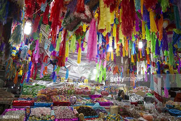 A vendor selling candy pinatas and other items waits for shoppers at her stand in the Jamaica Market in Mexico City Mexico on Wednesday Dec 16 2015...
