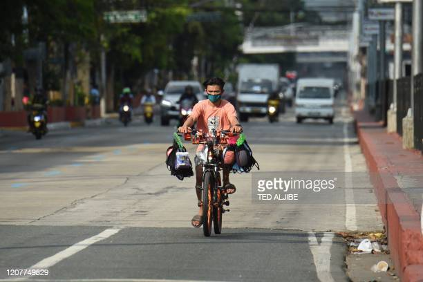 Vendor selling face masks travels down a road usually full of traffic in Manila on March 20 after the government imposed an enhanced community...