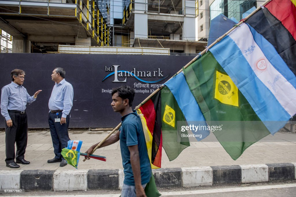 A vendor selling flags ahead of the 2018 FIFA World Cup Russia walks past a construction site in Dhaka, Bangladesh, on Wednesday, June 6, 2018. The Bangladesh economy will expand 6.9% this financial year and 6.8% in 2019, according to asurveyconducted by Bloomberg News. Photographer: Ismail Ferdous/Bloomberg via Getty Images