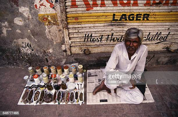 A vendor selling medicinal dried herbs in the street Mumbai India