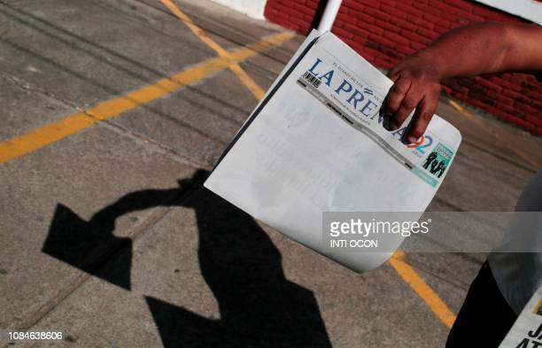 A vendor selling newspapers shows the edition of La Prensa which on January 18 2019 published its cover in blank in protest against the refusal by...