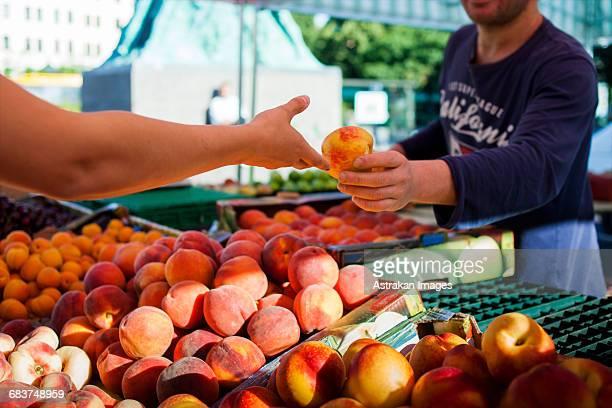 vendor selling peach to girl at market - bancarella foto e immagini stock