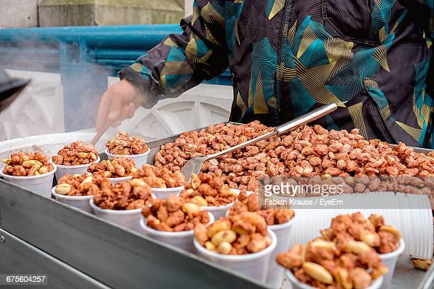 Vendor Selling Peanuts In Plastic Cups At Market Stall