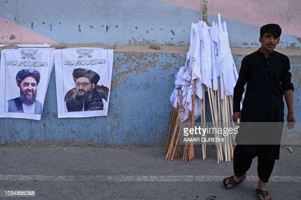Vendor selling Taliban flags stands next to posters of Taliban leaders Mullah Abdul Ghani Baradar and Amir Khan Muttaqi as he waits for customers...