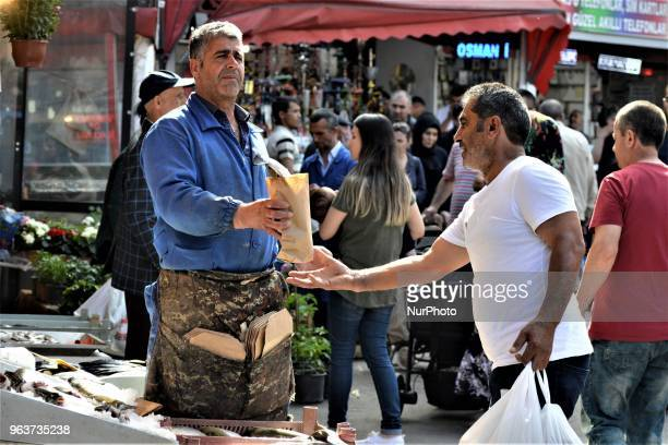 A vendor sells a fish to a customer in a bazaar during the Muslim holy fasting month of Ramadan in the historic Ulus district of Ankara Turkey on May...