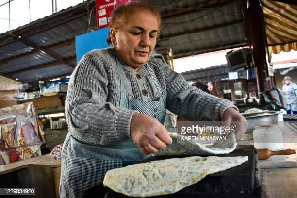 Vendor sells a traditional bread at a street market in Karabakh's main city Stepanakert on November 28 after six weeks of fighting between Armenia...