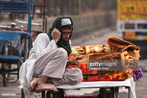 A vendor sells blankets on a roadside on a cold day on December 12 2017 in New Delhi India