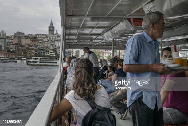 A vendor sells drinks on a ferry boat crossing the Bosphorus Strait as the Galata tower stands beyond in Istanbul Turkey on Friday Aug 17 2018...
