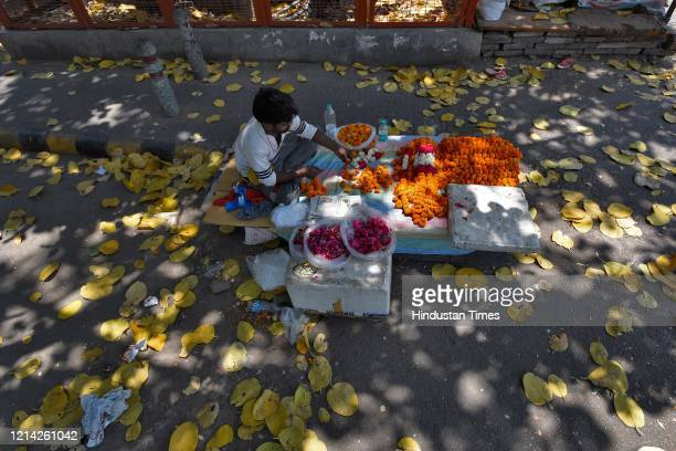 A vendor sells flowers after government eased lockdown restriction at Yusuf Sarai on May 20 2020 in New Delhi India