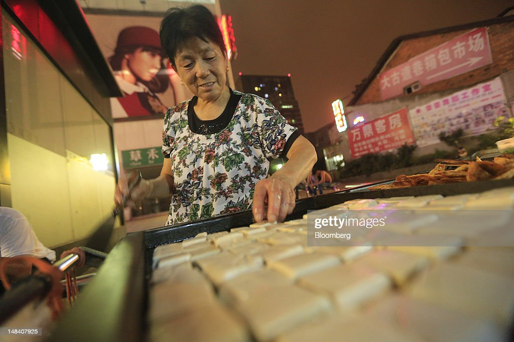 A vendor sells food at a night market in Changsha, Hunan Province, China, on Friday, July 13, 2012. Gross domestic product (GDP) expanded 7.6 percent in the second quarter of 2012 from a year earlier, China's National Bureau of Statistics said today in Beijing. Photographer: Nelson Ching/Bloomberg via Getty Images
