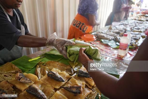 A vendor sells food wrapped in a banana leaf at the Port Vila Central Market on November 30 2019 in Port Vila Vanuatu Vendors no longer use singleuse...
