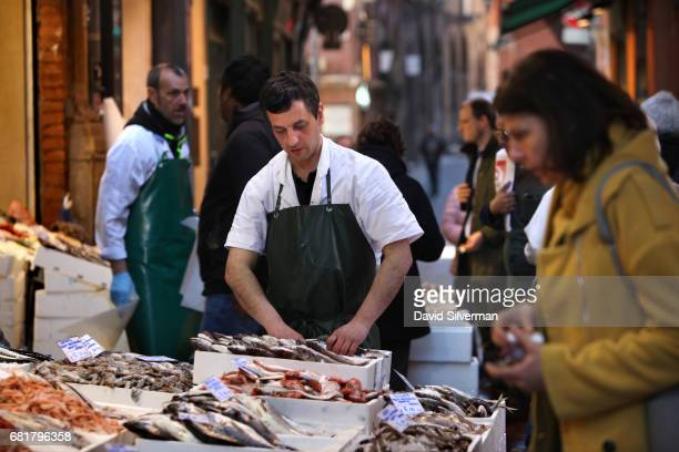 A vendor sells fresh fish and seafood at a stall in the ancient Quadrilatero market on March 30 2017 in Bologna Italy The cobblestone alleyways of...